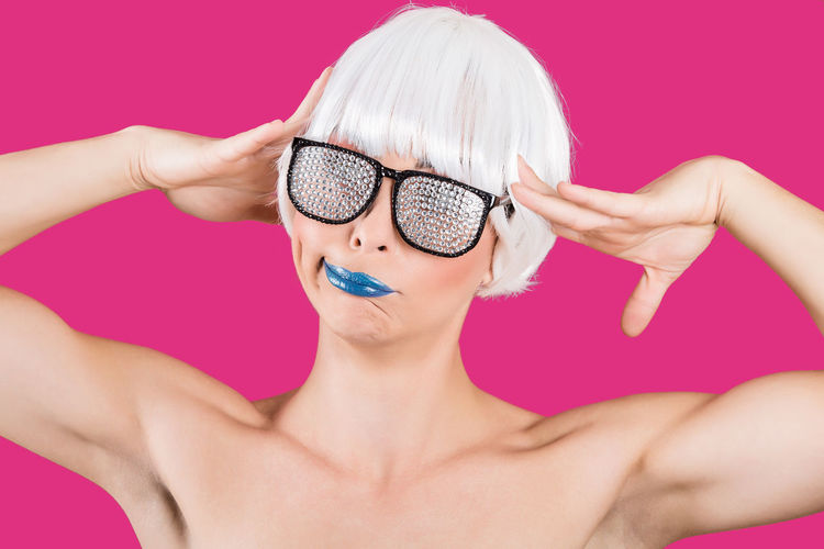 Woman wearing wig and trendy silver glasses grimacing on pink background.