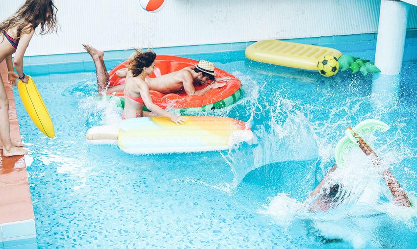 Friends enjoying on pool rafts in swimming pool