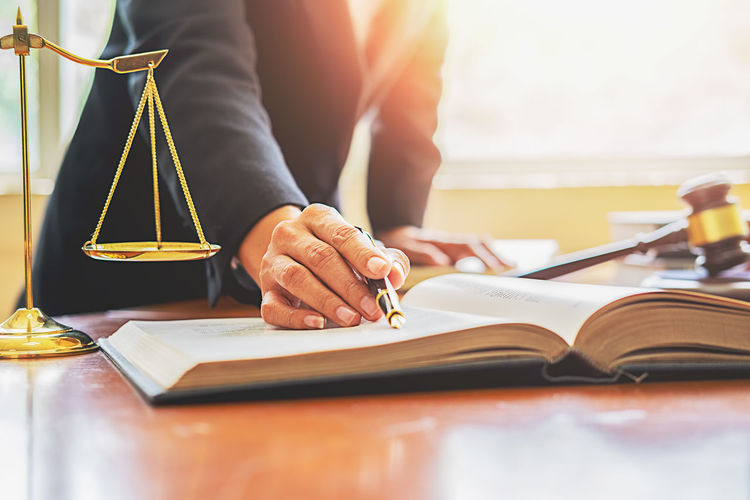 Midsection of lawyer reading book on table in office