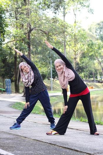 Sisters wearing hijab while exercising by lake at park