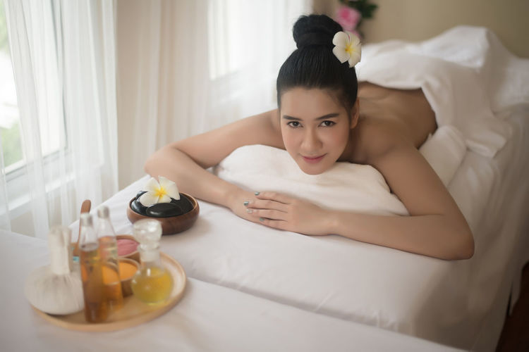 Portrait of smiling young woman lying on massage table in spa