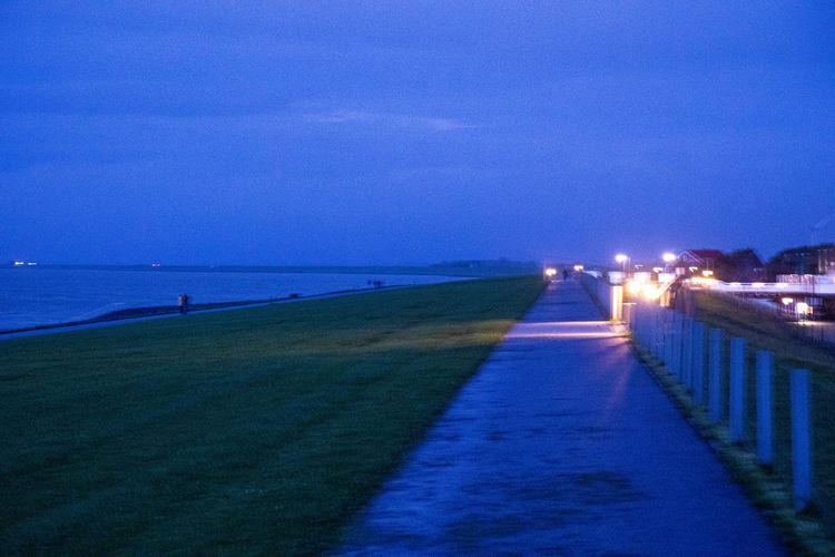Illuminated street by sea against sky at night
