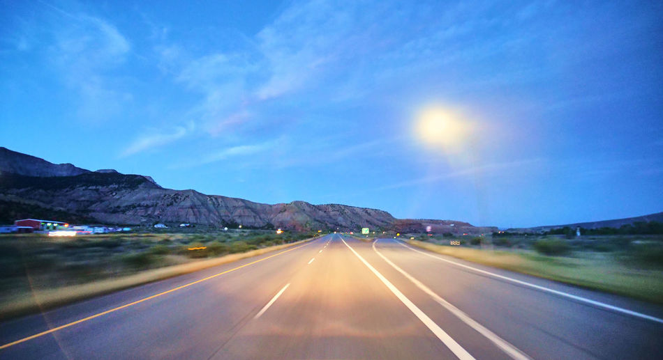 Transportation Road Sky Mountain Symbol Direction The Way Forward Sign Road Marking No People Nature Diminishing Perspective Marking Sunlight Mountain Range Landscape Cloud - Sky Scenics - Nature Tranquility vanishing point Outdoors Sun Dividing Line Lens Flare