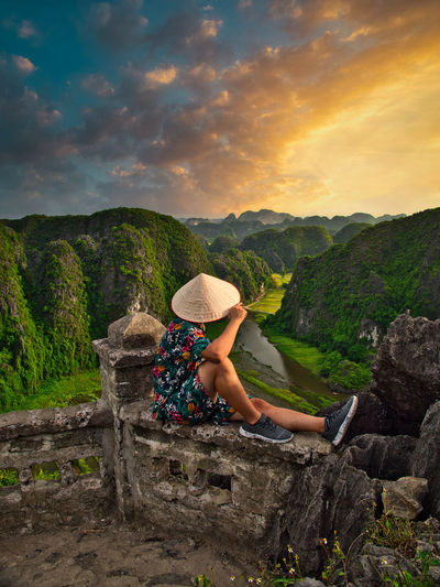 Woman sitting on land against mountain range against sky