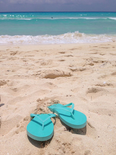 Land Beach Sea Water Sand Horizon Blue Horizon Over Water Nature Sky Beauty In Nature Tranquility No People Shoe Day Tranquil Scene Sandal Pair Scenics - Nature Turquoise Colored Outdoors Slipper