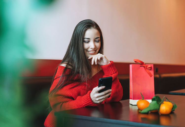 Beautiful asian woman in red clothes using mobile with gift bag in cafe, chinese new year