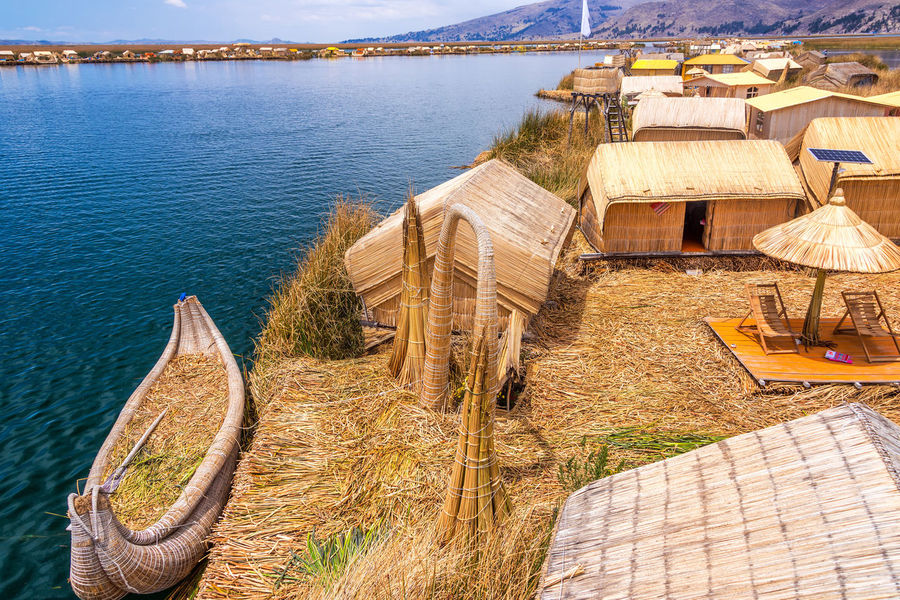 Manmade Uros floating islands and reed boat boat near Puno, Peru on Lake Titicaca America Andes Boat Destination Floating Inca Lake Landscape Latin Native Nature Peru Peruvian Puno Puno, Perú Reed Scenic Sky Titicaca Titicaca Lake Totora Travel Uros Uros Island Water
