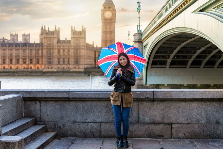Portrait of young woman holding umbrella while standing against thames river in city