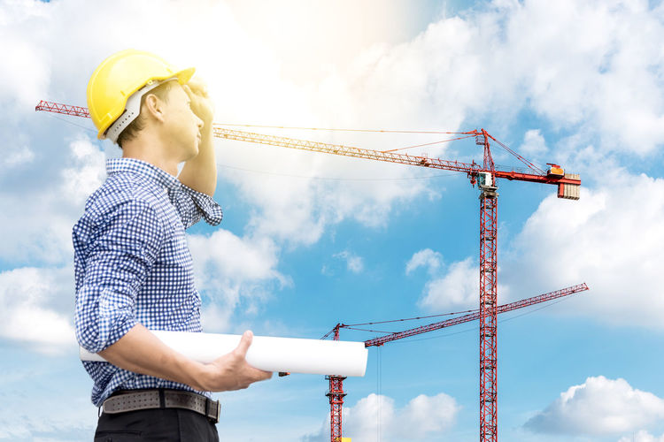 Architect With Blueprint Against Sky At Construction Site