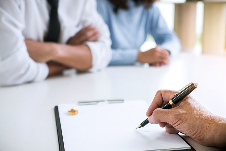 Cropped Hand Of Lawyer Signing Divorce Paper By Couple Sitting On Desk