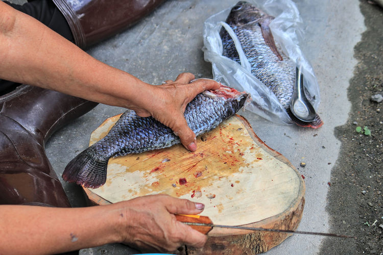 The cook was cutting the tilapia and cleaning it. to prepare dinner