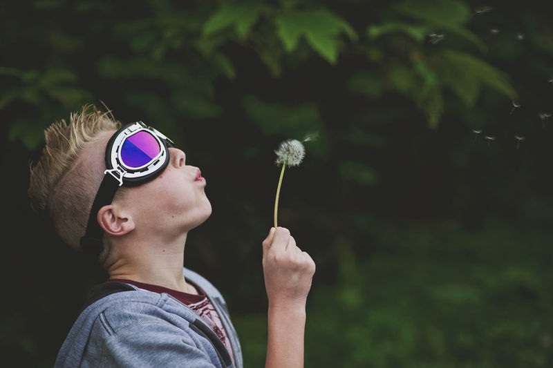 Making a childhood wish Dreaming Making A Wish Blowing Boys Childhood Dandelion Day Elementary Age Emotion Flower Focus On Foreground Headshot Leisure Activity Lifestyles Nature One Person Outdoors People Real People Sunglasses