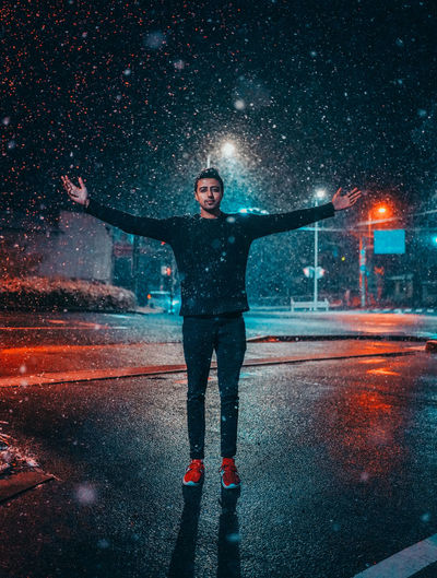 Full length of man with arms outstretched standing on street during snowfall