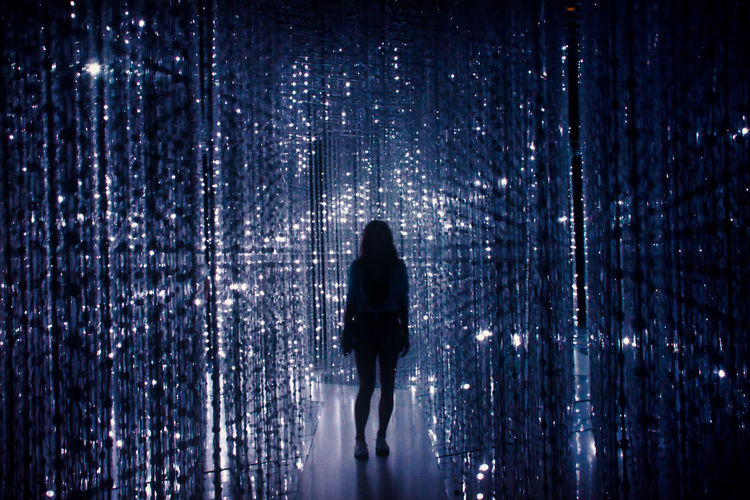 Silhouette of woman standing on walkway amidst illuminated beaded curtains