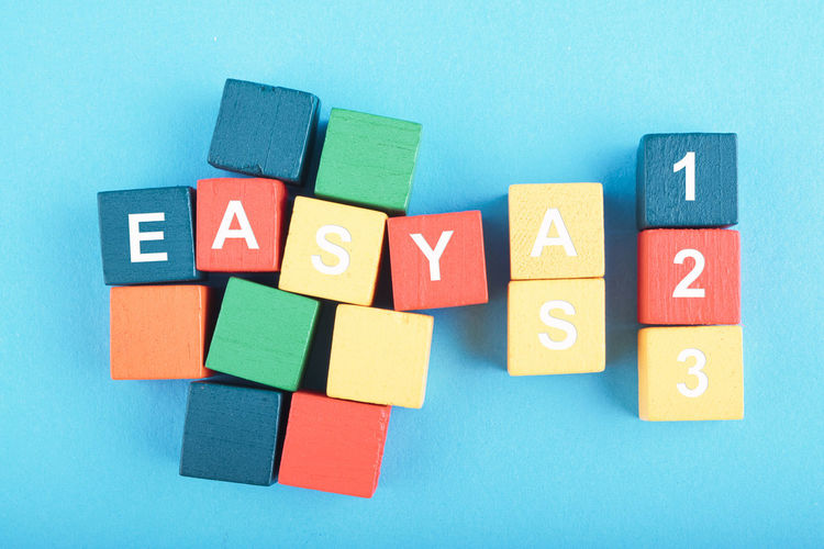 EASY AS 123 word on wooden cube over blue background Multi Colored Indoors  Childhood Toy Block Toy Studio Shot Still Life Blue Learning Group Of Objects Close-up Large Group Of Objects Education Directly Above Text Creativity Variation Cut Out Choice Blue Background
