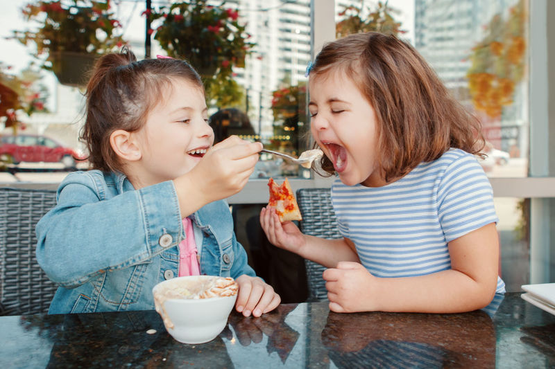 Happy girl feeding food to sister at restaurant