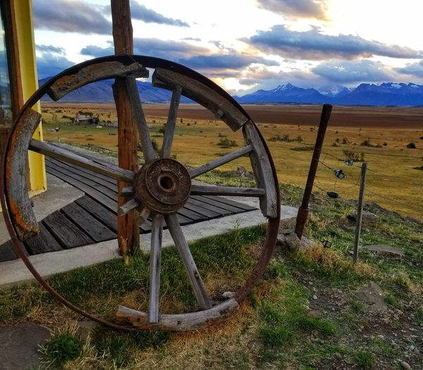 Abandoned wheel on field against sky
