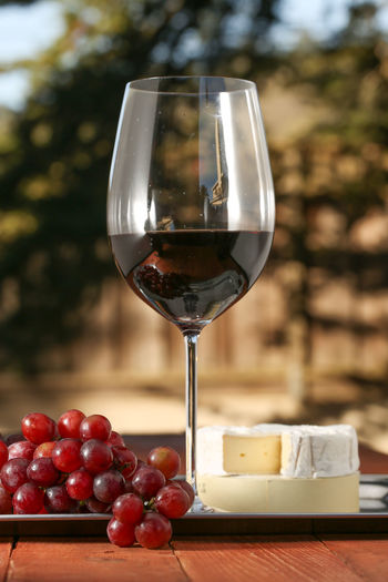 Close-Up Of Wineglass With Grapes And Cheese On Table