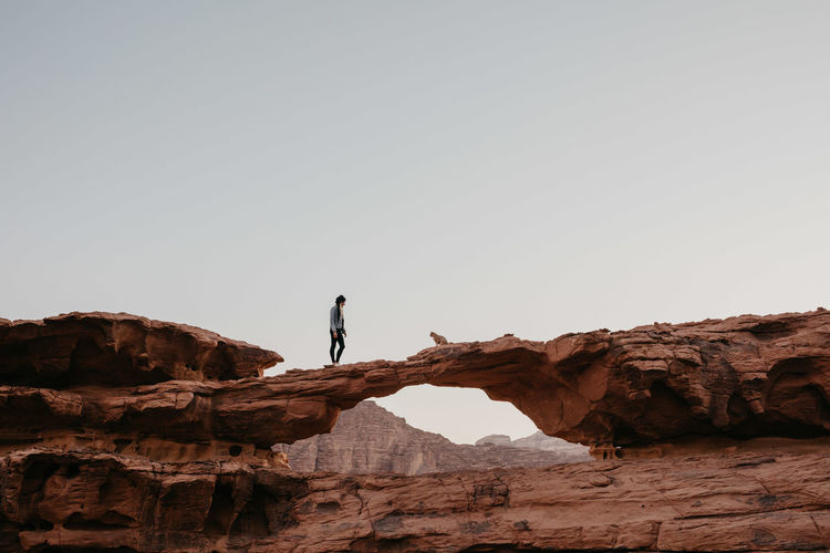 Mid distance of woman walking on rock formation against sky