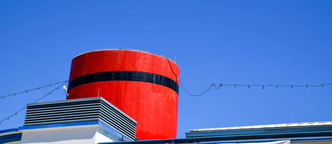Low angle view of red building against clear blue sky