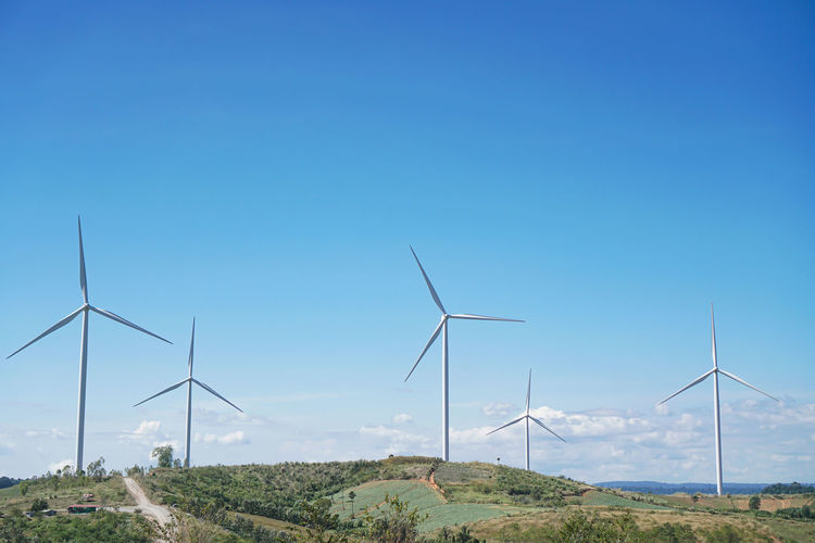 Wind turbines on field against clear blue sky