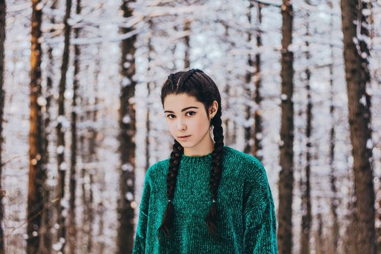 Portrait of young woman standing against tree trunk