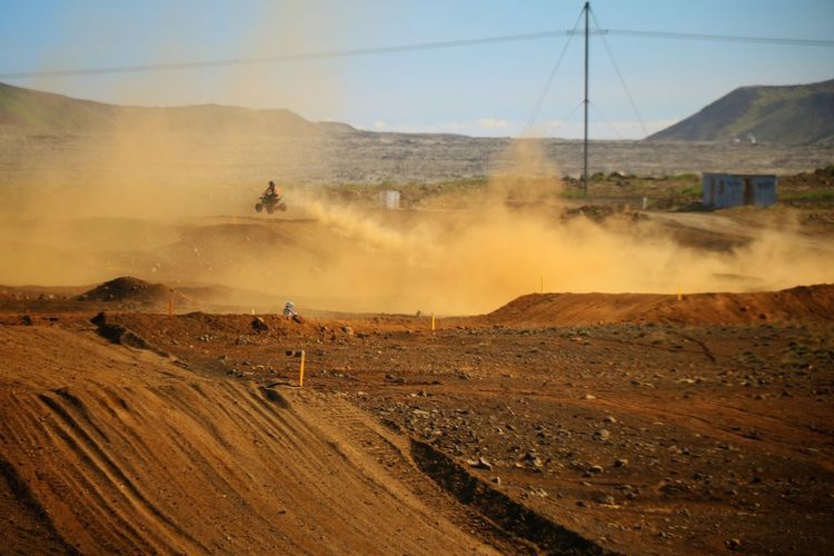 Motorcycle racing on dirt road