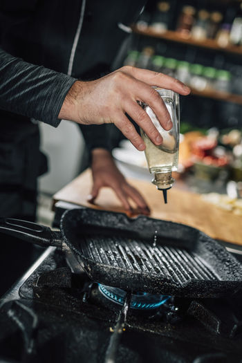 Restaurant cooking - chef pouring oil into a pan