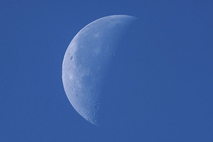 Low angle view of half moon against clear blue sky