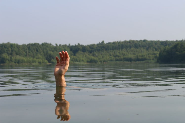 Cropped hand of person drowning in lake