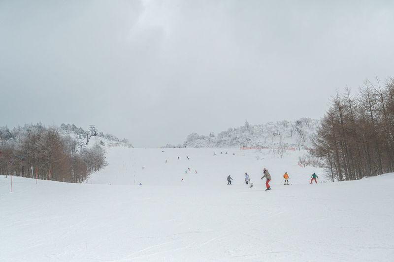 People skiing on snow field against sky