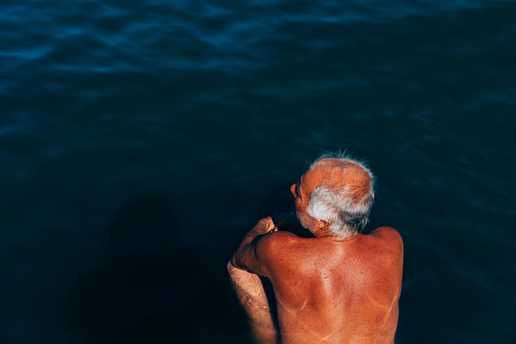 Rear View Of Shirtless Man Crouching By Sea