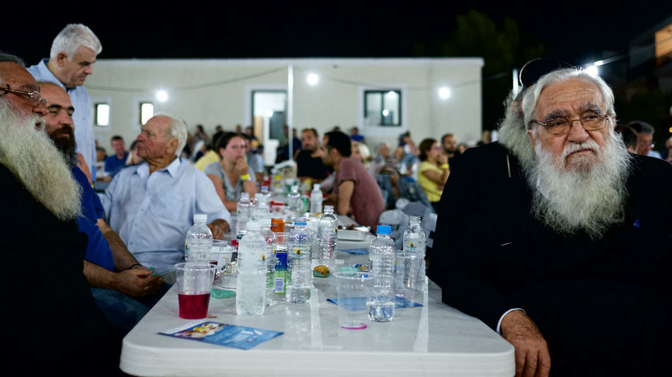 Beard Blackandwhite Dining Festival Food And Drink Greece Illuminated Large Group Of People Leisure Activity Lifestyles Lindos Men Old Man Orthodox Orthodox Church Person Priest Religion Religious  Rhodes Sitting Social Gathering Water Bottle  White Beard