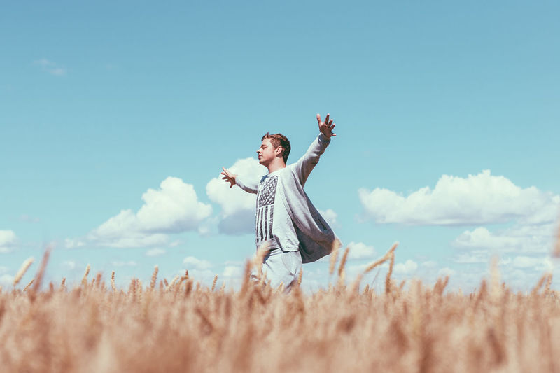 Young woman with arms raised on field against sky