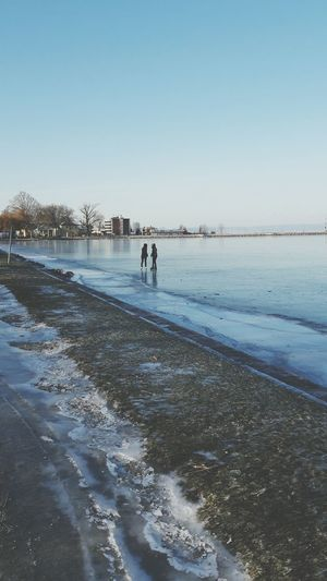People walking on beach against clear sky during winter