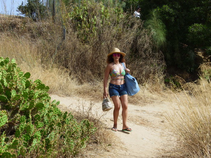 Mid adult woman wearing hat walking on hill against plants at beach