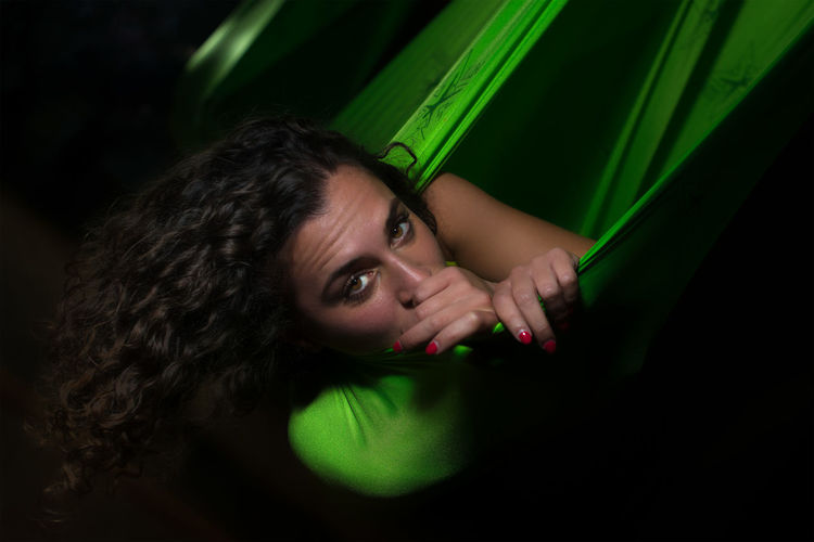 Portrait of beautiful woman lying on hammock in darkroom