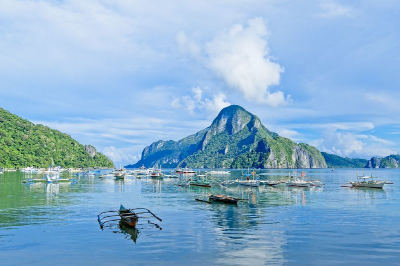 Palawan Philippines Water Nautical Vessel Transportation Mountain Cloud - Sky Sky Beauty In Nature Mode Of Transportation Day Scenics - Nature Nature Waterfront Mountain Range Sea Non-urban Scene Tranquility Reflection Tranquil Scene Outdoors Palawan Philippines Ocean Boat Resort