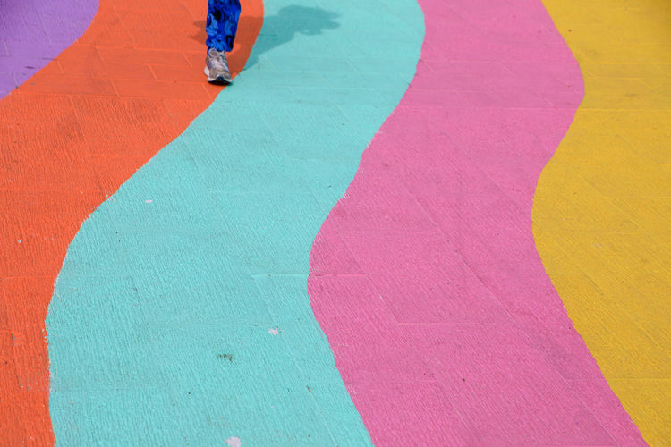Runner on colourful path Blue Body Part Day High Angle View Human Body Part Human Leg Leisure Activity Lifestyles Low Section Men Multi Colored Outdoors People Real People Sport Standing Unrecognizable Person Walking Women