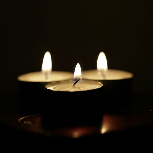 Lit Tealight Candles In Dark Room