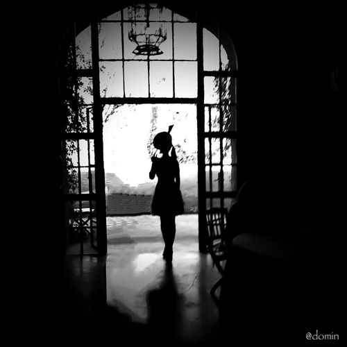 Silhouette of woman standing in glass window