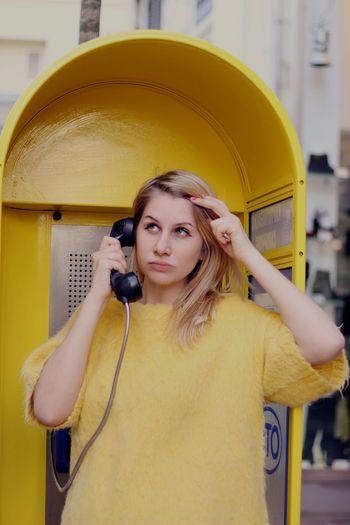 Young Woman Talking On Telephone Booth