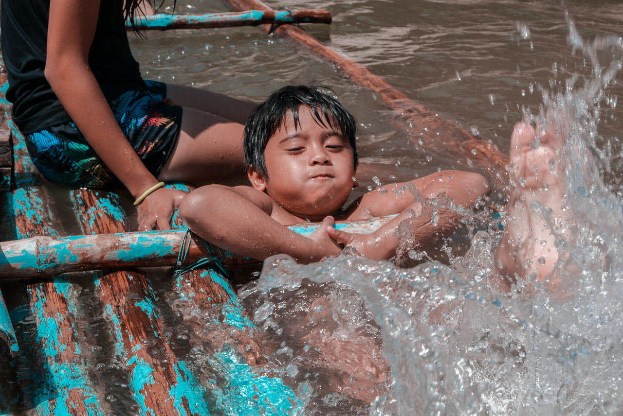 real people, leisure activity, childhood, lifestyles, one person, water, swimming pool, outdoors, day, boys, young adult, people