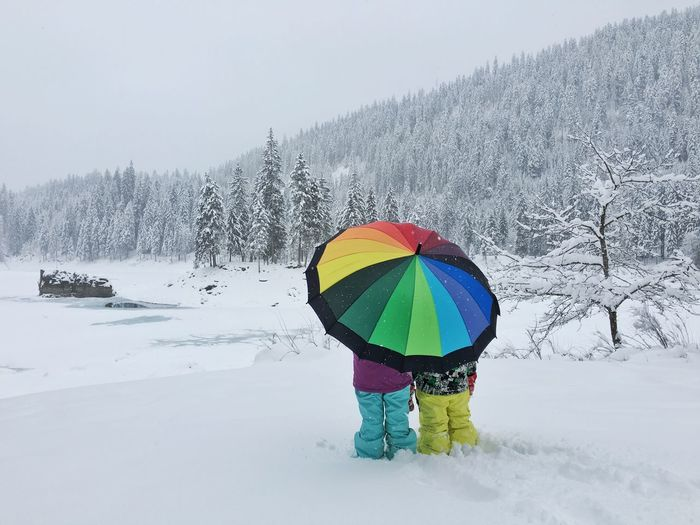 Rear view of people standing with colorful umbrella in blizzard