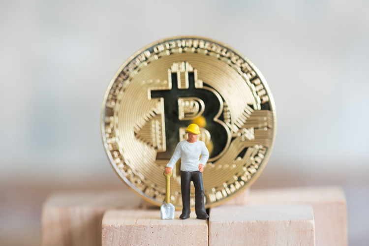Close-up of male worker figurine with bitcoin on wood