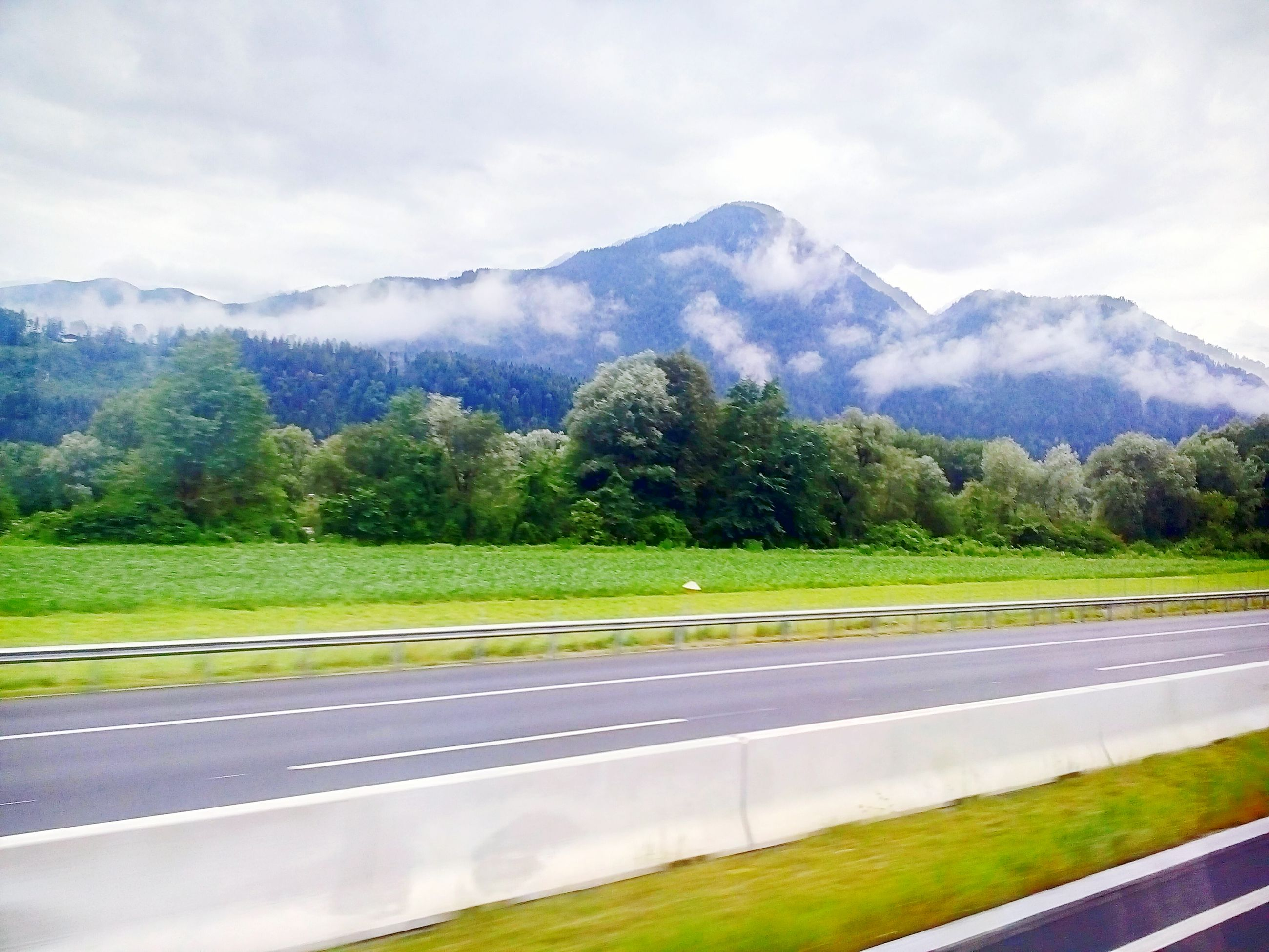 mountain, road, empty, tranquil scene, tree, street, tranquility, transportation, landscape, scenics, road marking, solitude, nature, mountain range, long, beauty in nature, country road, green color, pathway, non-urban scene, majestic, outdoors, cloud, white line, countryside, day, in front of, the way forward, remote, sky, narrow, empty road, growth, cloud - sky