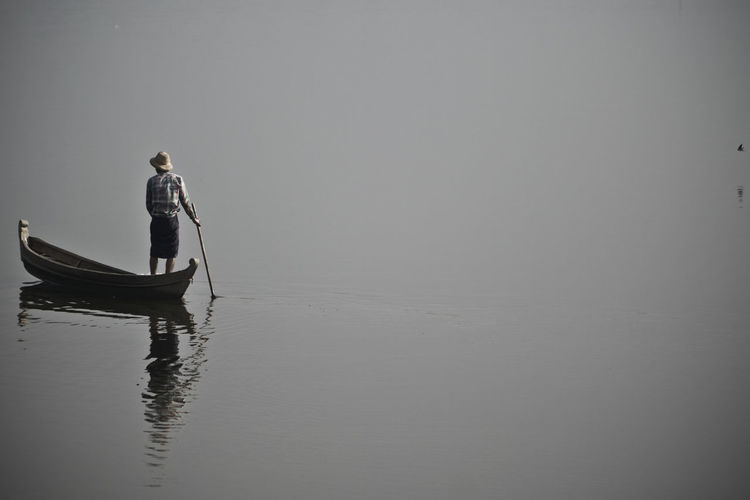 Rear view of fisherman standing on boat at lake