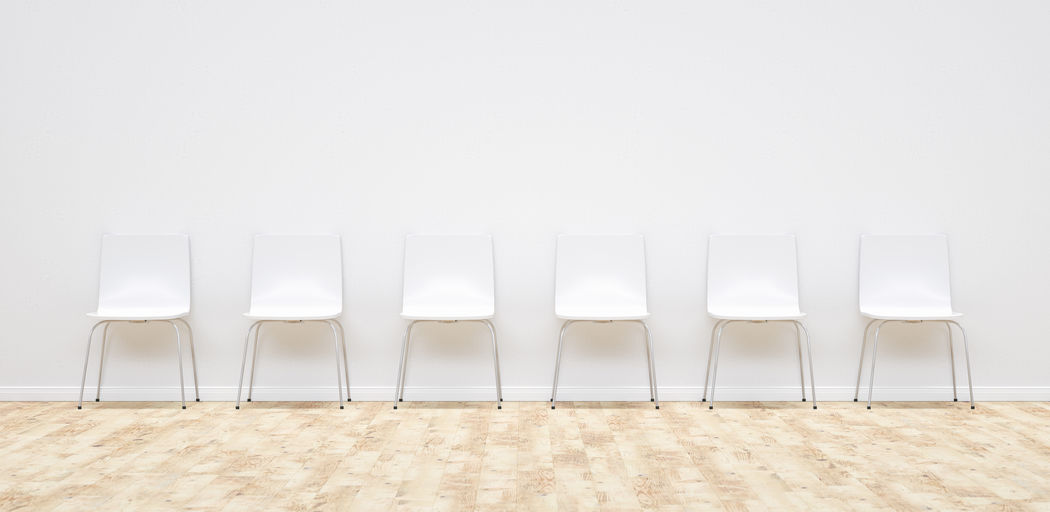 Row of empty chairs by wall