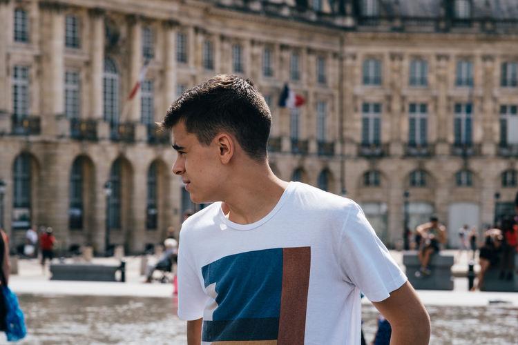 Teenage boy looking away while standing in city