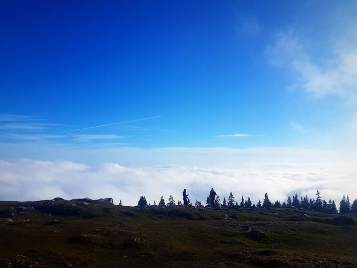People on land against blue sky